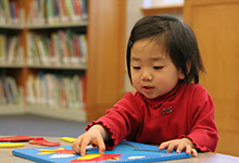 A preschooler works on a puzzle.